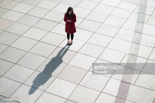 businesswoman using smartphone and standing on concrete floor - mirar hacia abajo fotografías e imágenes de stock