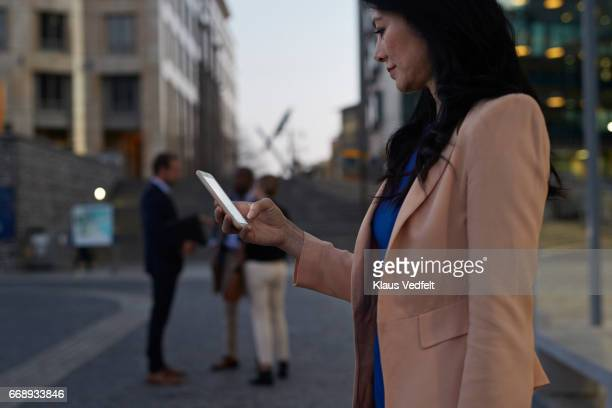 Businesswoman using smartphone at taxi pickup