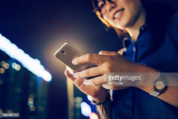 Businesswoman using smartphone in city at night