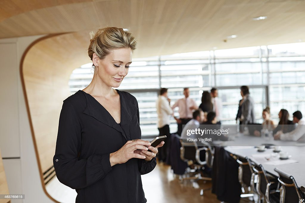 Businesswoman using smartphone in conference room : Stockfoto