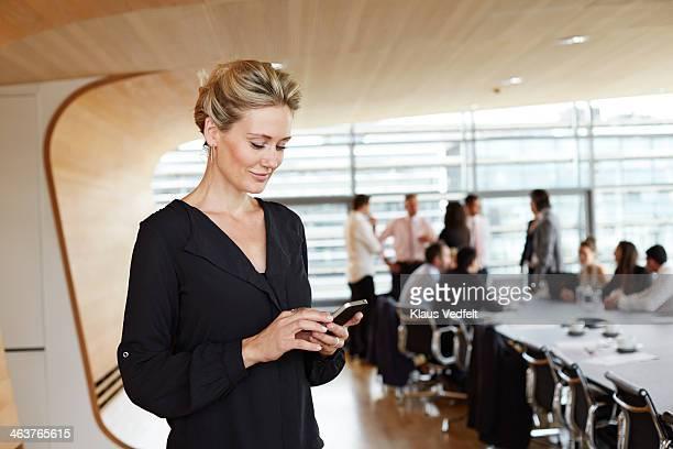businesswoman using smartphone in conference room - incidental people stockfoto's en -beelden