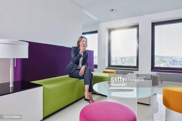businesswoman using smartphone in office lounge - hocker stock-fotos und bilder