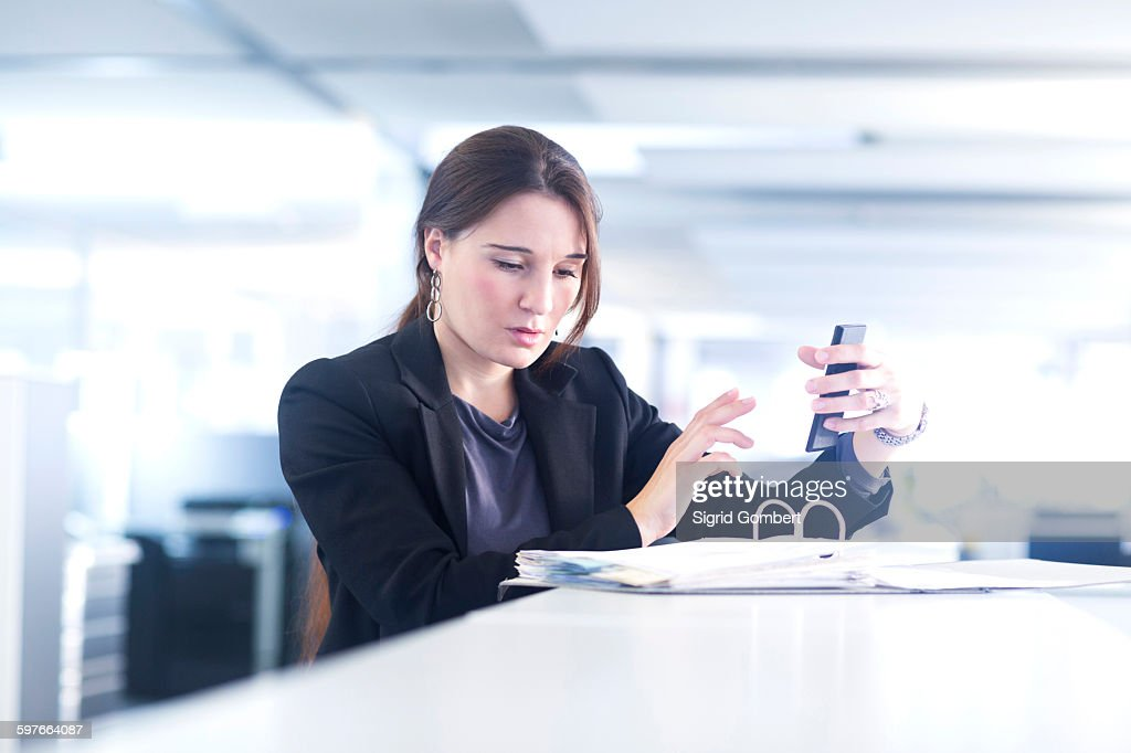 Businesswoman using smartphone in office : Stock-Foto