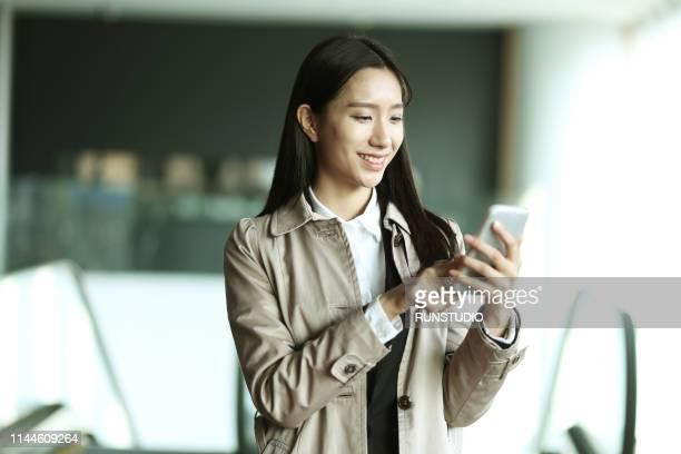 businesswoman using smartphone inside office building - see ストックフォトと画像