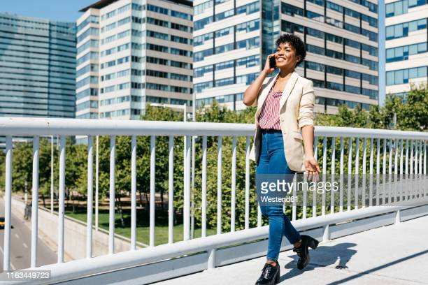 businesswoman using smartphone, office buildings in the background - 歩道橋 ストックフォトと画像