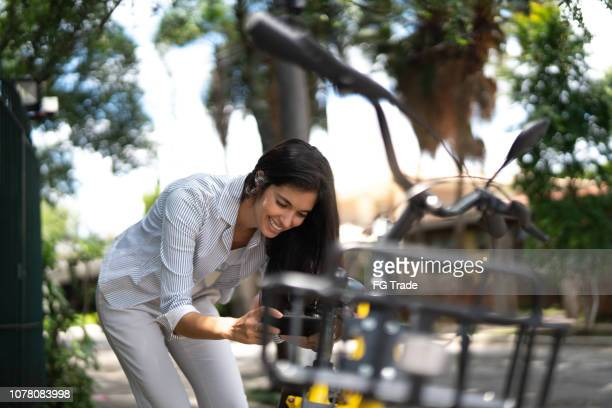 businesswoman using smartphone scanning the qr code of shared bike in the city - bicycle parking station stock photos and pictures