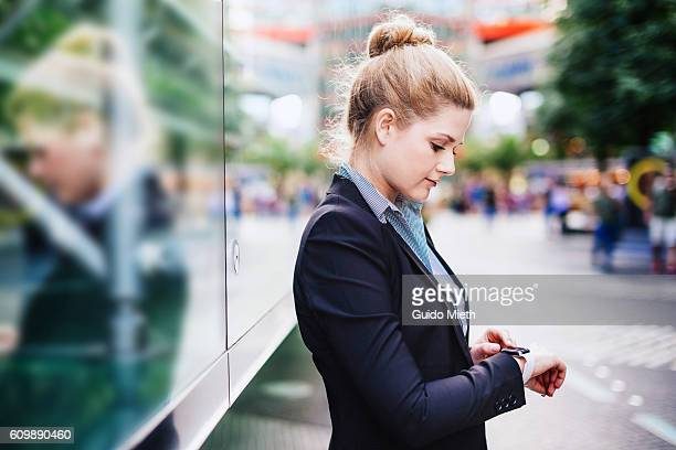businesswoman using smartwatch in city. - geschäftskleidung stock-fotos und bilder