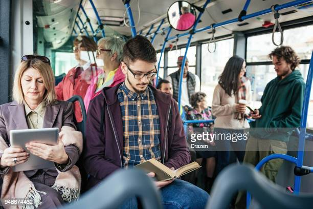 businesswoman using tablet and student reading book in the bus - affollato foto e immagini stock