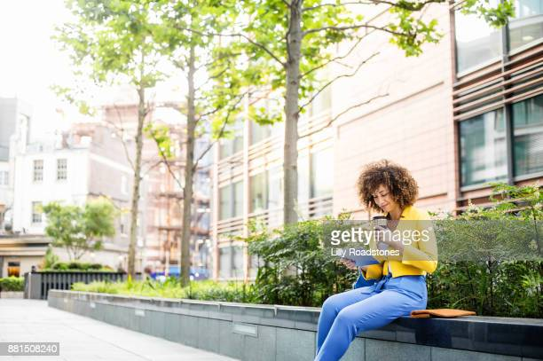 Businesswoman using tablet computer outdoors
