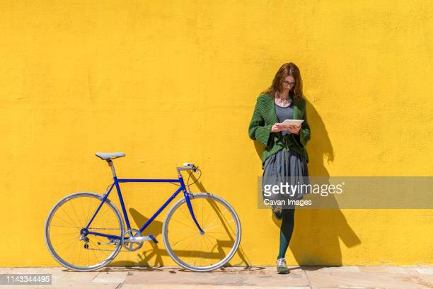 businesswoman using tablet computer while standing on sidewalk by bicycle against yellow wall during sunny day - lehnend stock-fotos und bilder