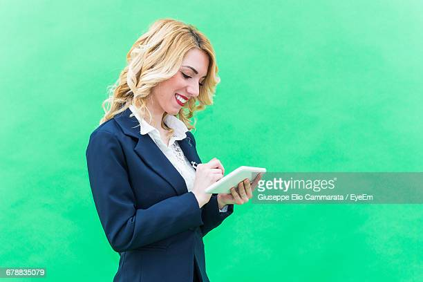 Businesswoman Using Tablet In Front Of Green Background