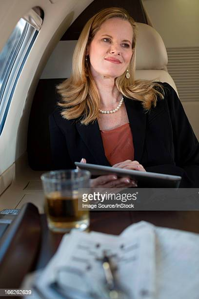 Businesswoman using tablet on airplane