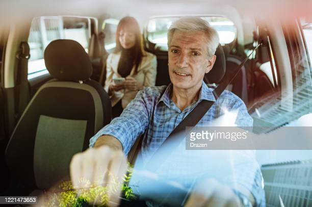 businesswoman using taxi ride to go to work, gray hair taxi driver with seat belt on - taxi driver stock pictures, royalty-free photos & images