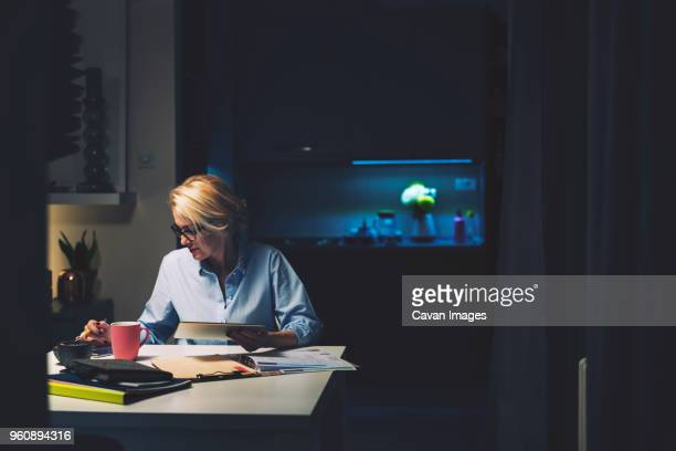 businesswoman using technologies while sitting at desk in home office - working late stock pictures, royalty-free photos & images