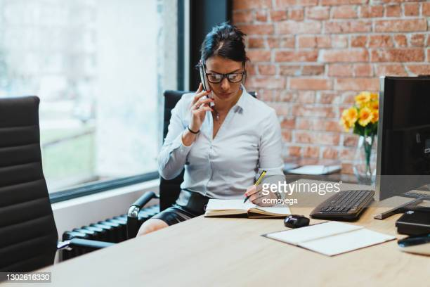 businesswoman using telephone and working in modern office - white shirt stock pictures, royalty-free photos & images