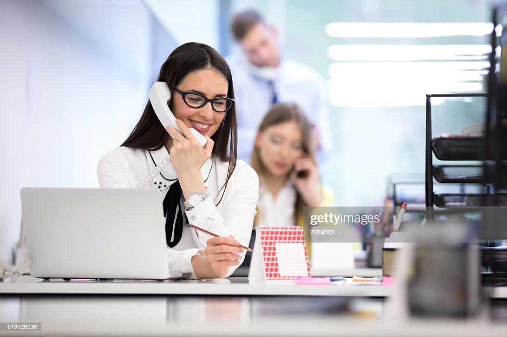 Geschäftsfrau auf Telefon am Schreibtisch in Büro : Stock-Foto