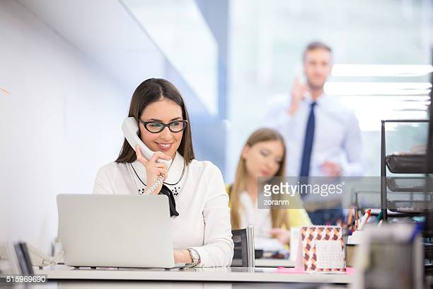 Businesswoman using telephone at desk in office