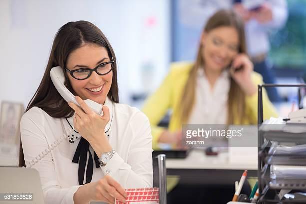 Mujer de negocios usando un teléfono en el escritorio de oficina