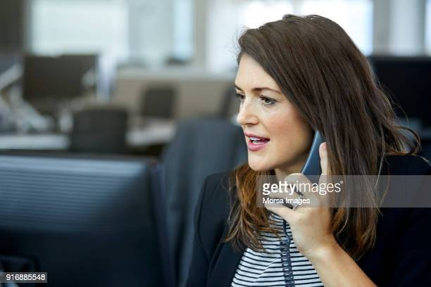businesswoman using telephone at desk - usare il telefono foto e immagini stock