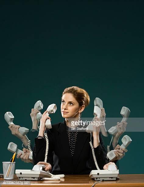 Businesswoman using telephone at desk (Multiple Exposure)