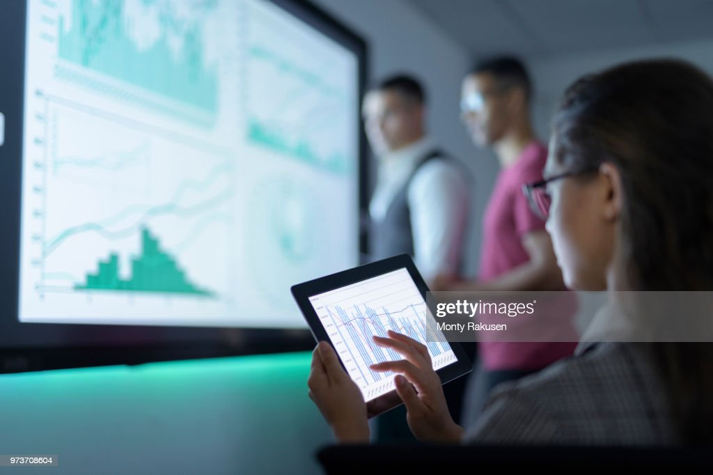 Businesswoman viewing graphs on digital tablet in business meeting : Stock Photo