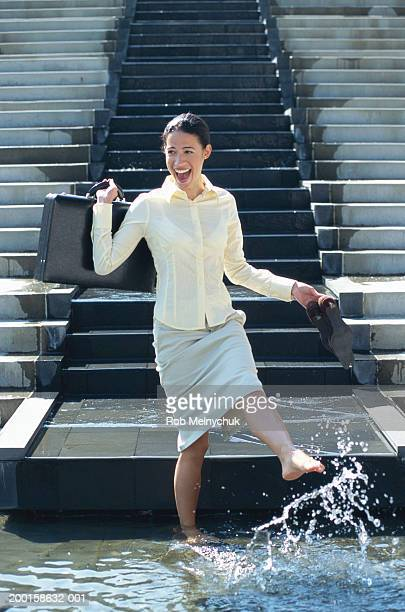 businesswoman wading in fountain, laughing - quitting a job stock pictures, royalty-free photos & images