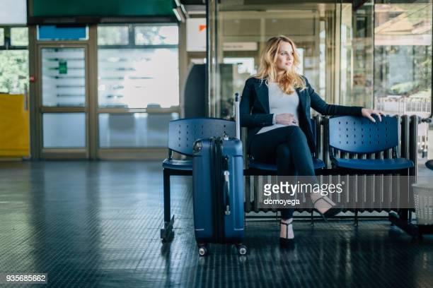 zakenvrouw wachten op haar vlucht op de luchthaven - netjes informeel stockfoto's en -beelden
