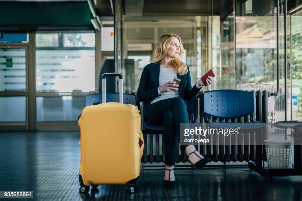 businesswoman waiting for her flight at the airport - baggage claim stock pictures, royalty-free photos & images