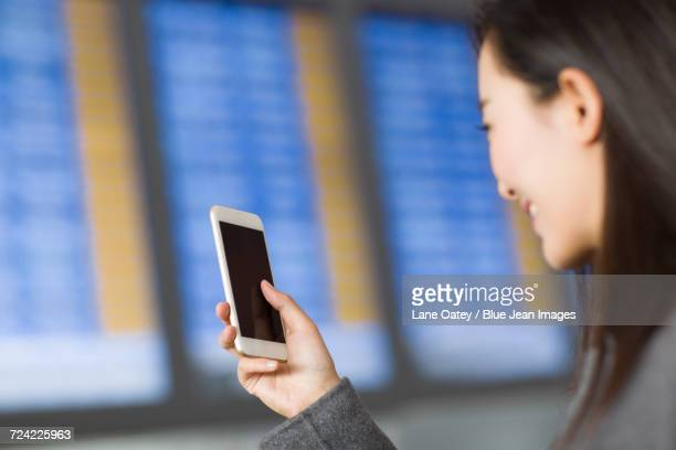 Businesswoman waiting in airport with smart phone