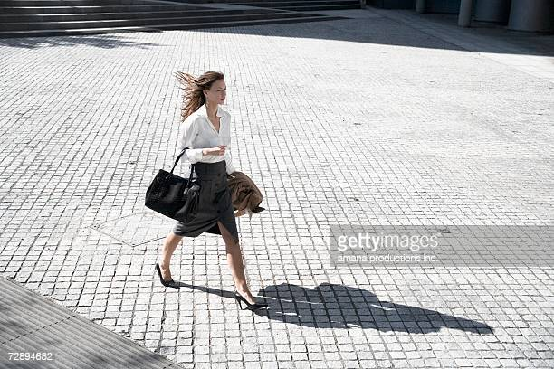 Businesswoman walking across public square (high angle view)