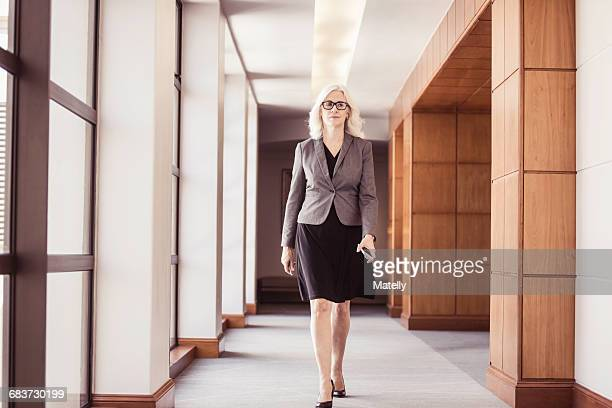 Businesswoman walking along office corridor