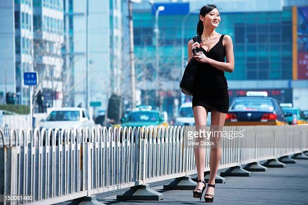 Businesswoman walking along street