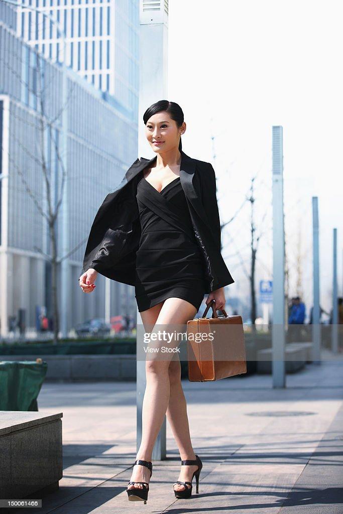 Businesswoman walking along street : Stock Photo