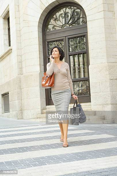 businesswoman walking along zebra crossing, using mobile phone - zebra crossing stock pictures, royalty-free photos & images