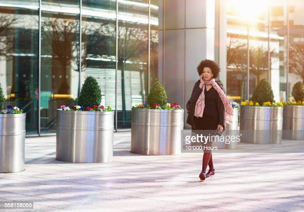 Businesswoman walking and using cellphone