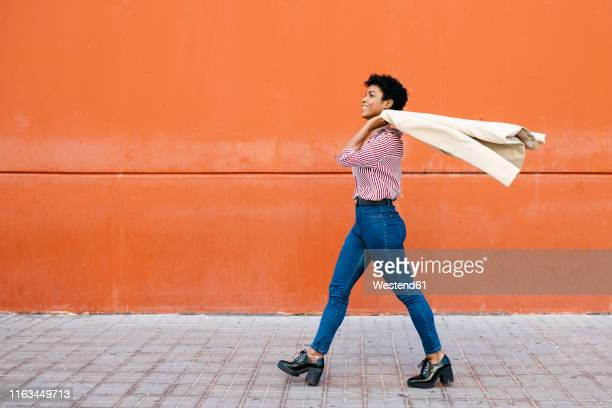 businesswoman walking at a red wall in the background, putting her jacket on her shoulder - marcher photos et images de collection