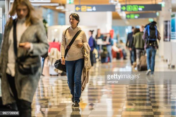 businesswoman walking at airport - beige purse stock pictures, royalty-free photos & images