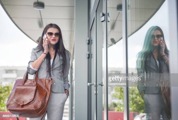Businesswoman walking beside office building, using smartphone