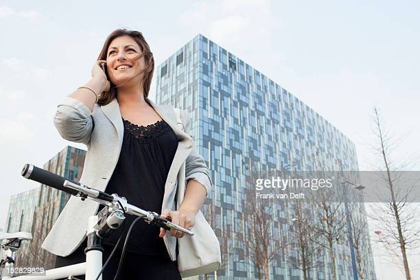 Businesswoman walking bicycle outdoors