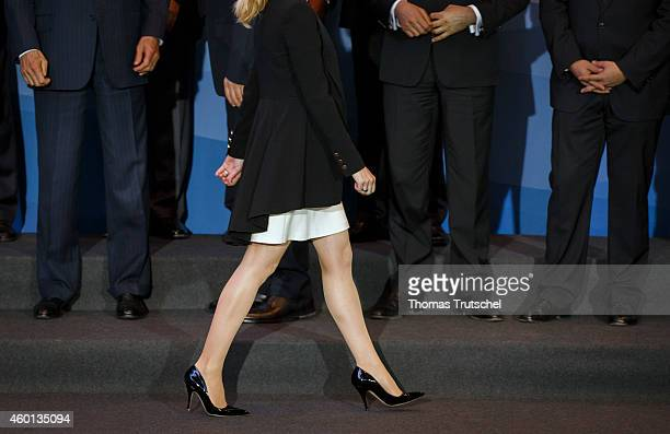 Businesswoman walking by a group of businessmen standing on a podium on December 04 in Basel Switzerland Photo by Thomas Trutschel/Photothek via...