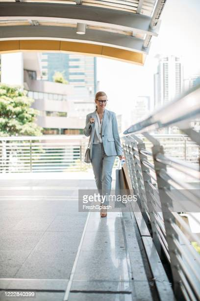 businesswoman walking carrying shopping bags - pump dress shoe stock pictures, royalty-free photos & images
