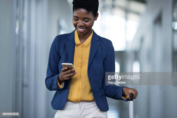 Businesswoman walking down hall way, looking at smartphone