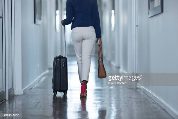 businesswoman walking down hall way with rolling suitcase - trousers stock pictures, royalty-free photos & images