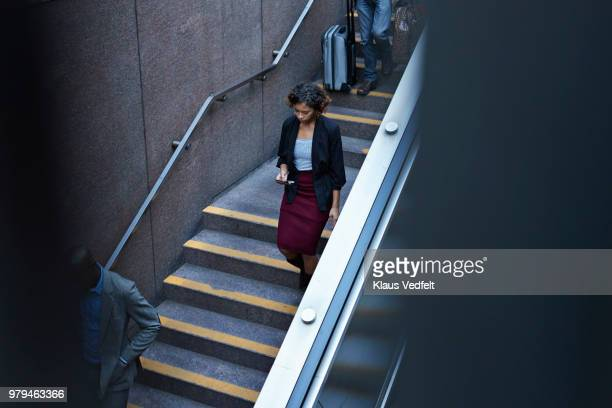Businesswoman walking down stairs to metro station and looking at smartphone