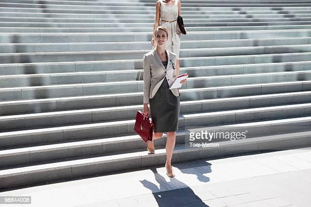 Femme d'affaires marchant le long de quelques marches en plein air