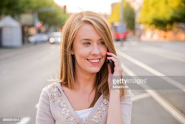 businesswoman walking down the street while talking on smart pho