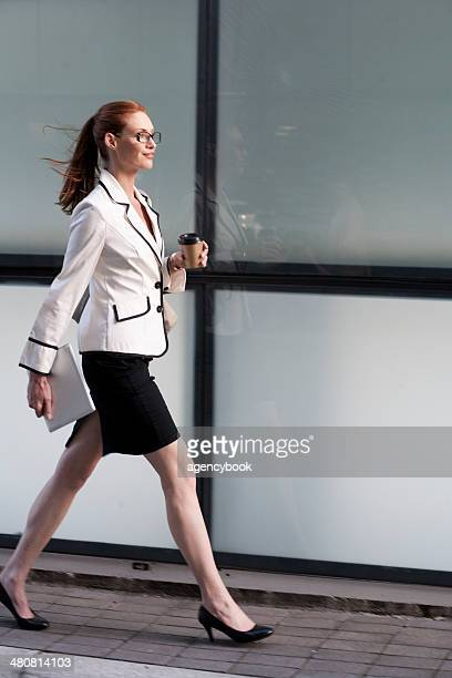 Businesswoman walking, holding hot drink and digital tablet