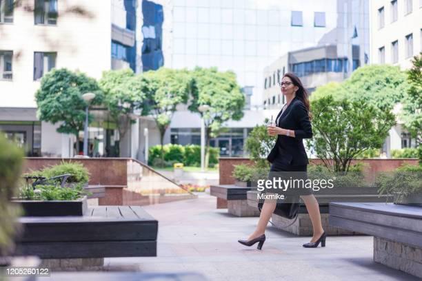 geschäftsfrau geht in eile mit frischem saft in der hand - büropark stock-fotos und bilder