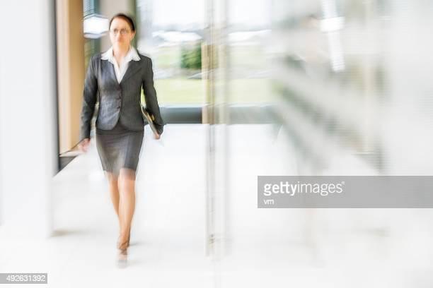 Geschäftsfrau zu Fuß in Büro-Korridor brighlty beleuchteten