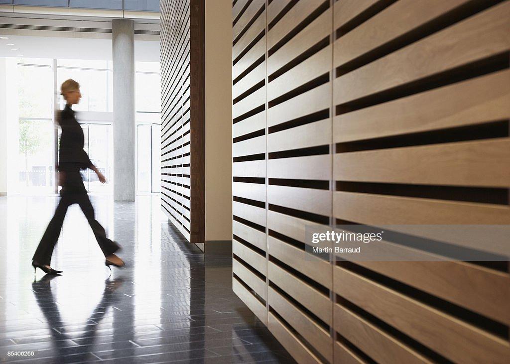 Businesswoman walking in corridor : Stock Photo